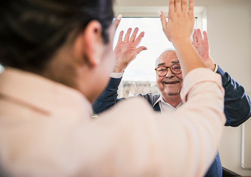 Happy senior man with raised hands looking at young woman - gettyimageskorea
