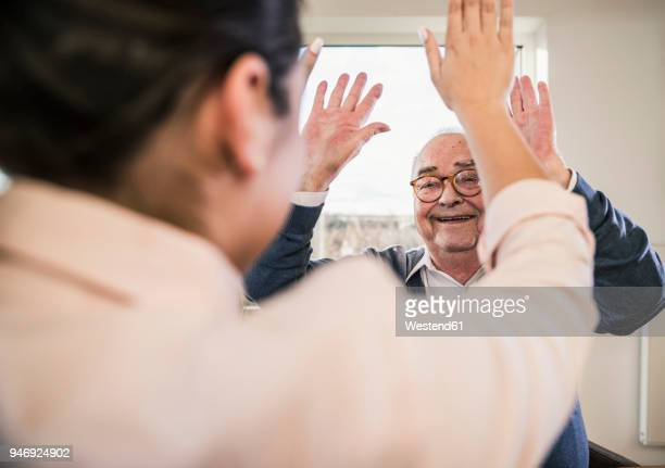 happy senior man with raised hands looking at young woman - mithilfe stock-fotos und bilder