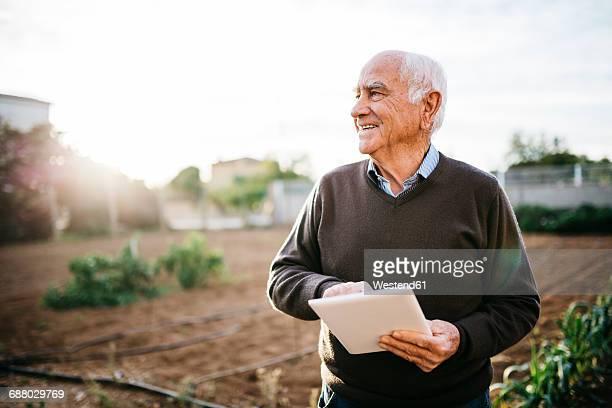 happy senior man with tablet in the garden - hombres mayores fotografías e imágenes de stock