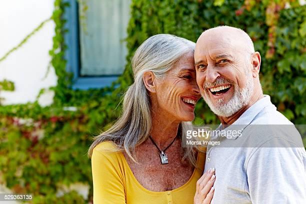 Happy senior man with woman at yard