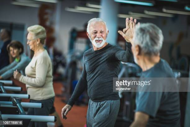 happy senior men giving each other high five on treadmills in a gym. - mature men stock pictures, royalty-free photos & images