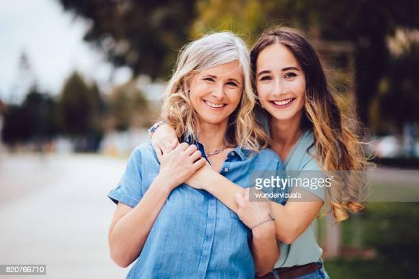Gelukkig senior moeder en dochter buitenshuis knuffelen
