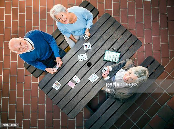 Happy senior people playing cards at table
