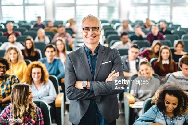 happy senior professor with large group of students in a lecture hall. - professor stock pictures, royalty-free photos & images