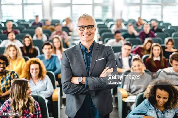 professeur principal heureux avec groupe important d'élèves dans une salle de conférences. - professeur d'université photos et images de collection