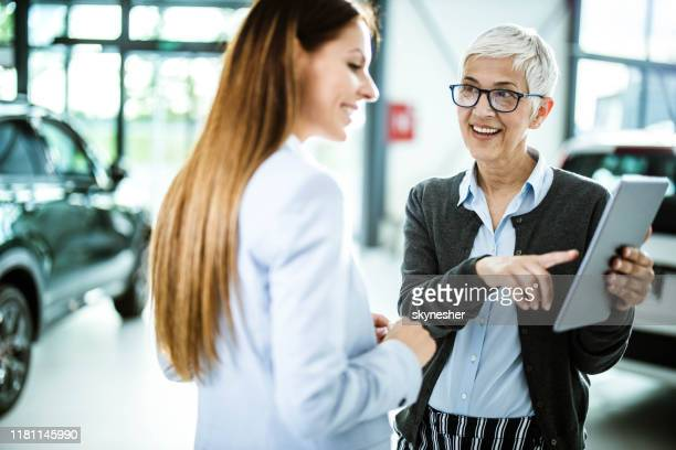 happy senior salesperson and her customer using touchpad in a car showroom. - customer focused stock pictures, royalty-free photos & images