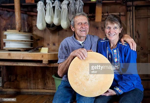 Happy Senior Schweizer Paar hält ein Laib Selfmade-Käse