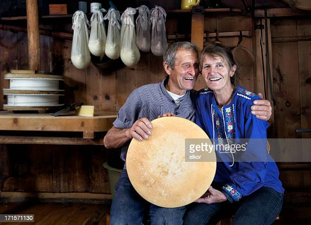 Happy Senior Swiss Couple Holding A Loaf Of Selfmade Cheese