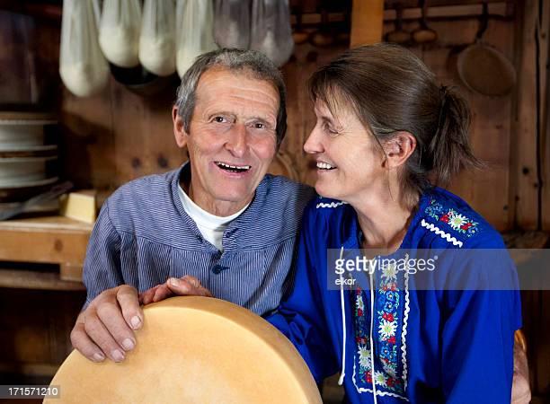 happy senior schweizer paar hält ein laib selfmade-käse - traditionelle kleidung stock-fotos und bilder