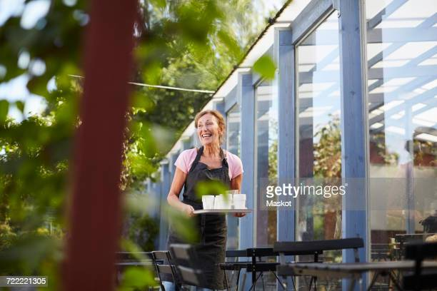 Happy senior waitress carrying disposable glasses on tray at sidewalk cafe