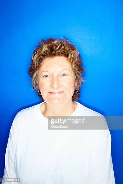 Happy senior woman against blue background