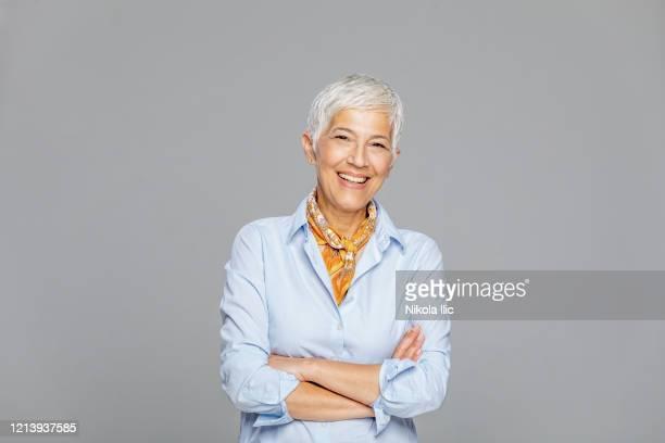 feliz mujer mayor sobre fondo gris. - retrato formal fotografías e imágenes de stock