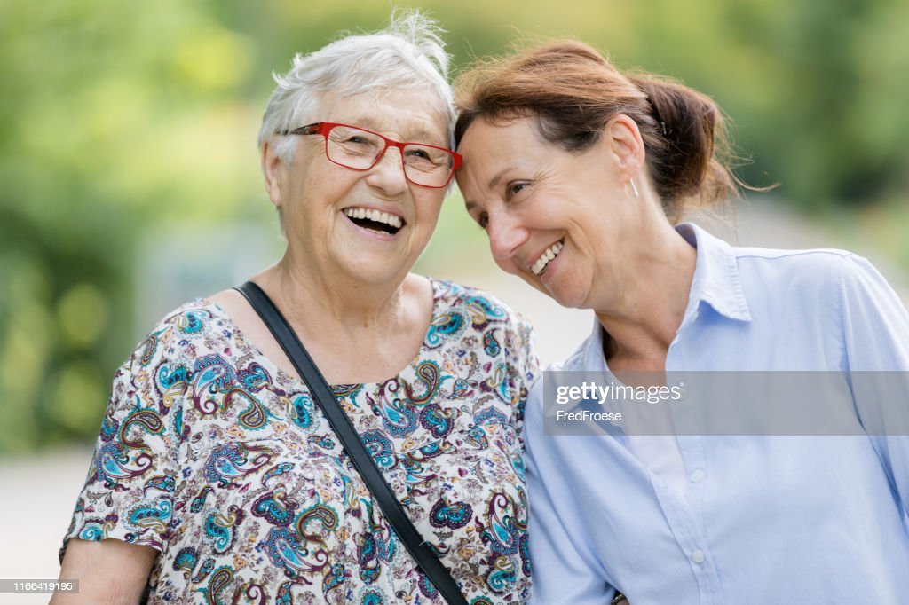 Happy senior woman and caregiver walking outdoors : Stock Photo