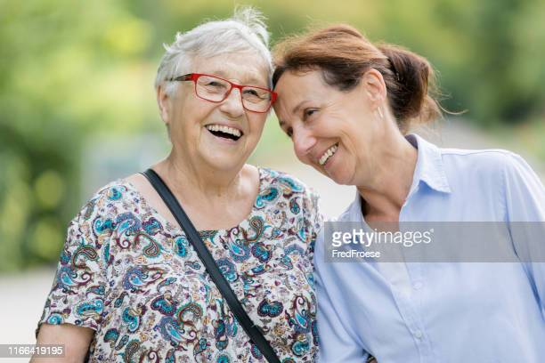 happy senior woman and caregiver walking outdoors - assistance stock pictures, royalty-free photos & images
