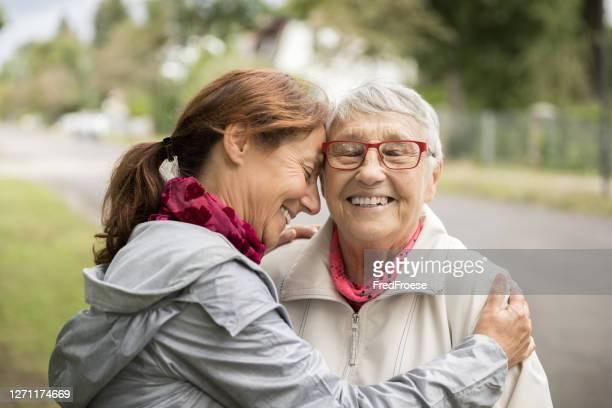 gelukkige hogere vrouw en caregiver die in openlucht lopen - volwassen nageslacht stockfoto's en -beelden