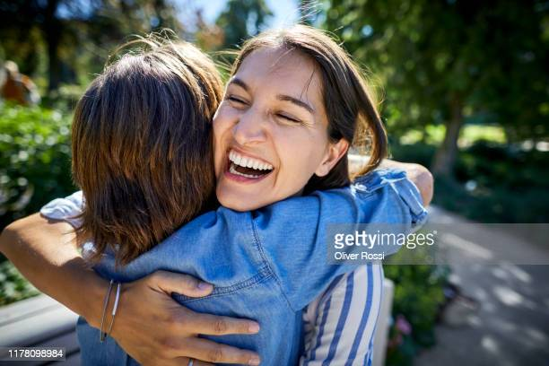 happy senior woman and her adult daughter hugging in a park - gratitude stock pictures, royalty-free photos & images
