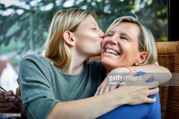 happy senior woman and young woman hugging and kissing in armchair - tochter stock-fotos und bilder