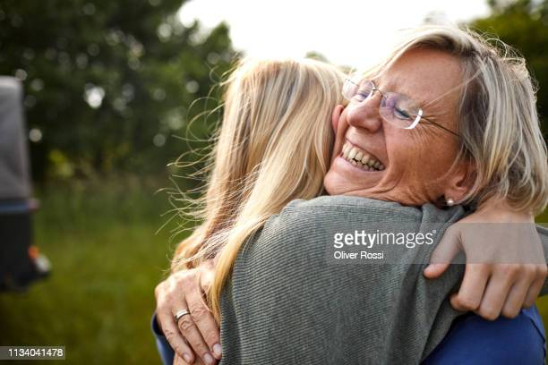 happy senior woman and young woman hugging outdoors with a jeep in background - umarmen stock-fotos und bilder