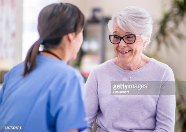 happy senior woman at doctor's office - hormone stock pictures, royalty-free photos & images