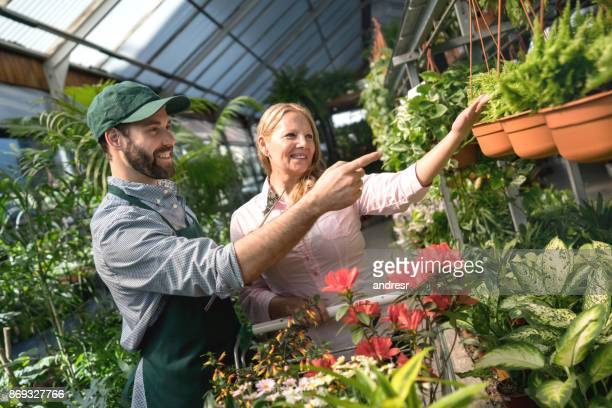 Happy senior woman buying plants at a greenhouse and salesman helping her both smiling