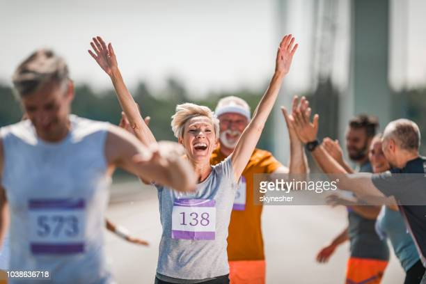 happy senior woman celebrating her end of marathon race. - spring racing stock photos and pictures