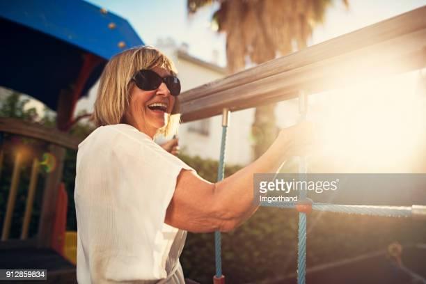 Happy senior woman climbing at the playground.