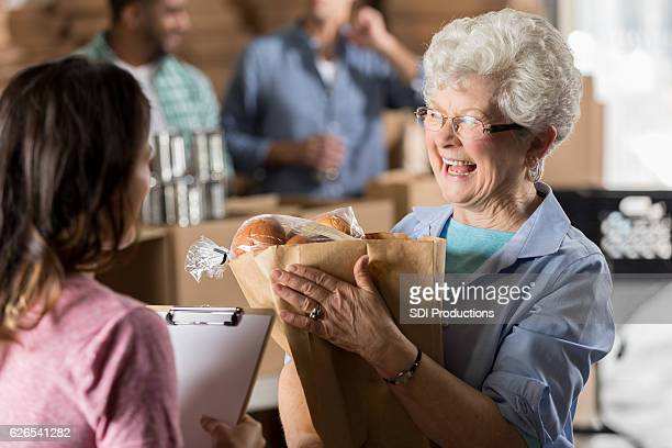 Happy senior woman donates groceries to food bank