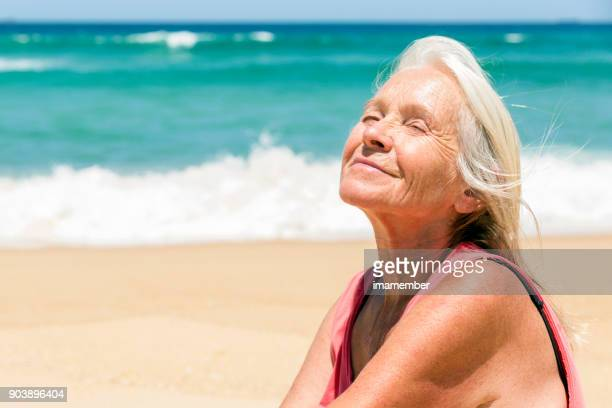 Happy senior woman dreaming on the beach, background with copy space