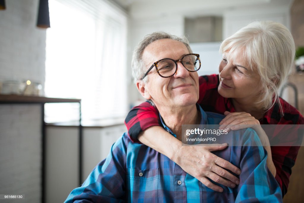 Happy senior woman embracing her husband : Foto de stock