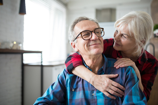 Happy senior woman embracing her husband 951685130