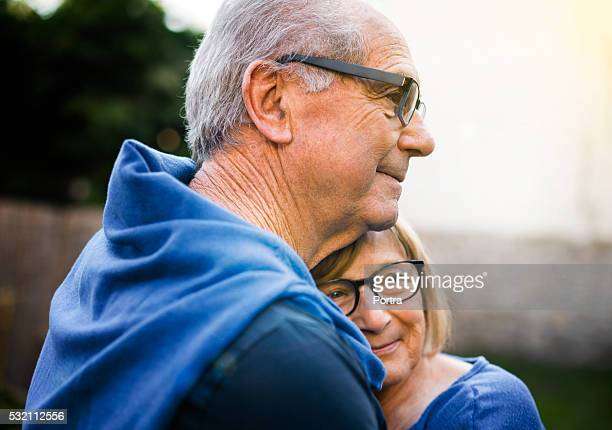 Happy senior woman embracing man in backyard