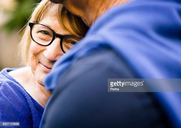 Happy senior woman embracing man outdoors