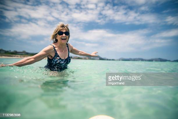 happy senior woman enjoying beach holiday - imgorthand stock photos and pictures