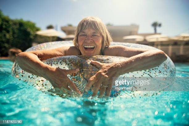 happy senior woman enjoying floating ring in swimming pool - rubber ring stock pictures, royalty-free photos & images