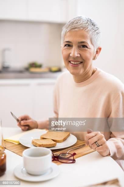 キッチンで朝食を楽しんで満足している年配の女性。