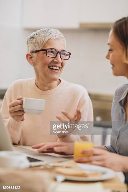 Happy senior woman enjoying in coffee time with her adult daughter.