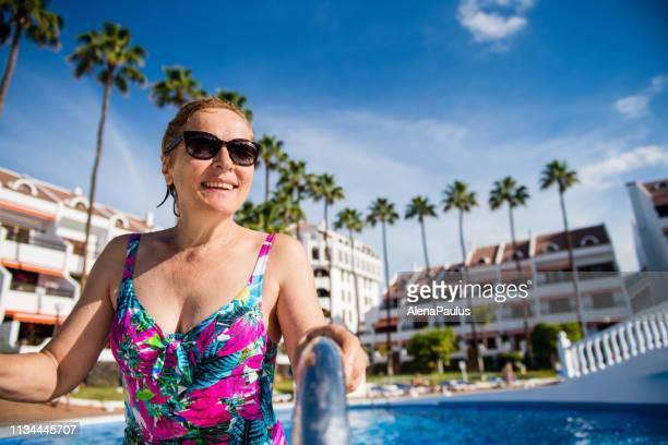 スイミングプールで楽しんで幸せなシニア女性 - テネリフェ島 ストックフォトと画像