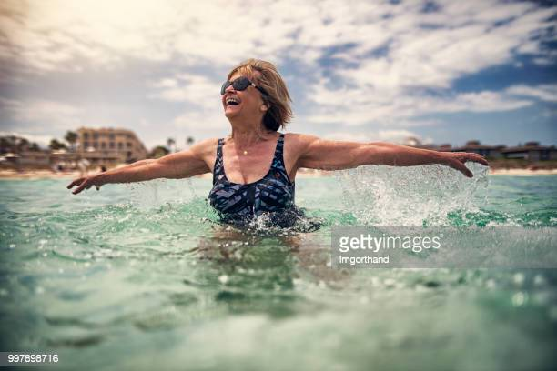 happy senior woman enjoying sea - wading stock pictures, royalty-free photos & images