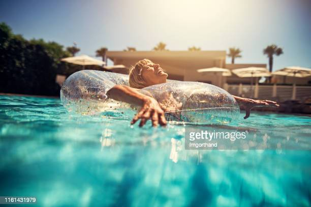 happy senior woman enjoying swimming pool - one senior woman only stock pictures, royalty-free photos & images