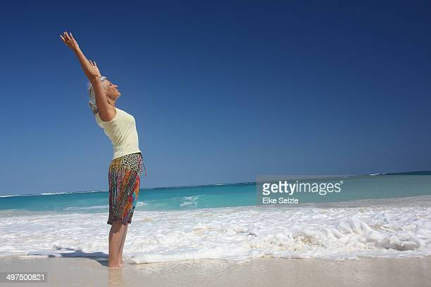 Happy senior woman enjoying the beach