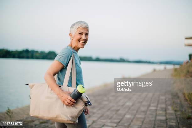 feliz mujer mayor terminando su formación - sporting term fotografías e imágenes de stock