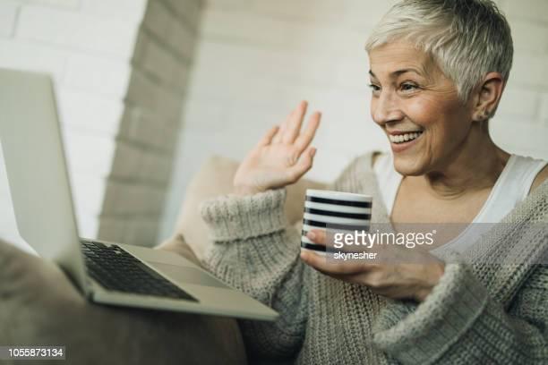 gelukkig senior vrouw die heeft een video-oproep over laptop thuis. - voip stockfoto's en -beelden