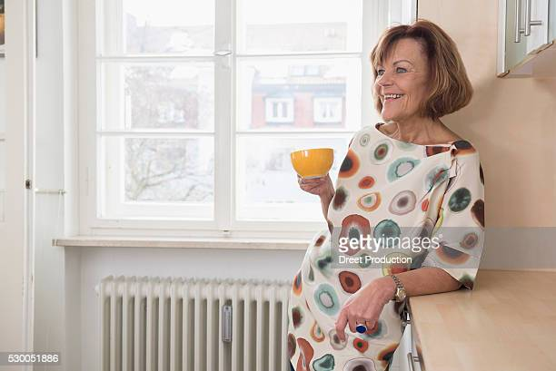 Happy senior woman having cup of tea in kitchen, Munich, Bavaria, Germany
