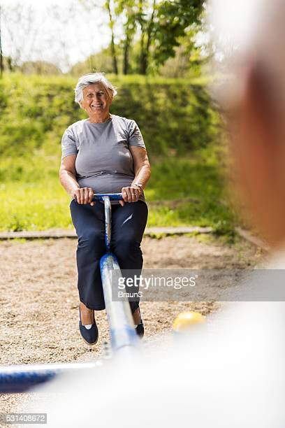 Happy senior woman having fun on a seesaw in nature.