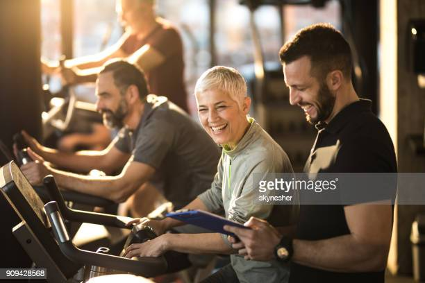 happy senior woman having fun with her coach on exercising class in a gym. - coach stock pictures, royalty-free photos & images