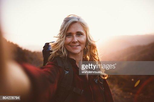 Happy senior woman hiker taking a selfie on mountain edge