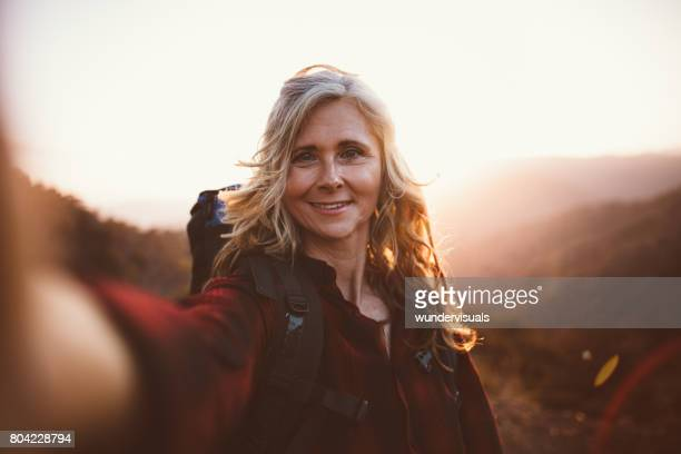 Happy senior woman hiker taking a selfie on mountain edge