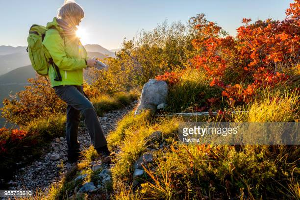 Happy Senior Woman Hiking at Autumnal Dawn in Julian Alps, Slovenia, Europe