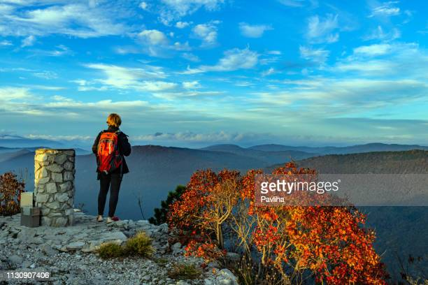 feliz mujer mayor senderismo en el amanecer otoñal en alpes julianos, italia, europa - formación karst fotografías e imágenes de stock