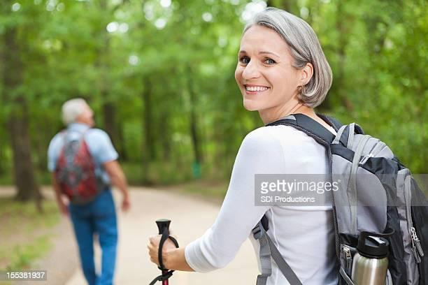 Happy senior woman hiking with husband